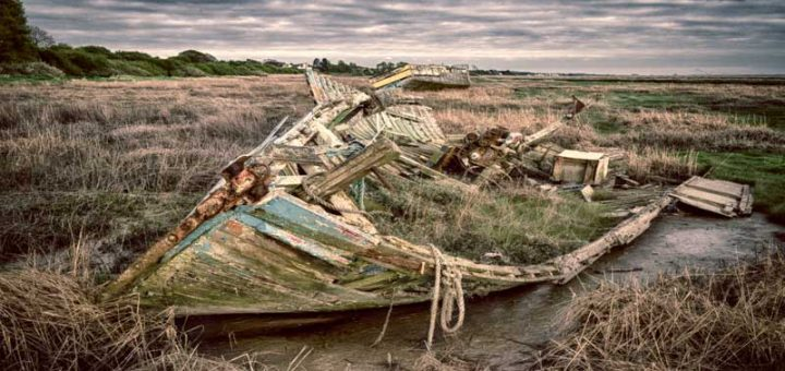 An old boat gradually decays into the mud, at Heswall